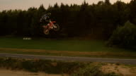 AERIAL SLOW MOTION: Extreme pro motocross biker jumping no footer big air video