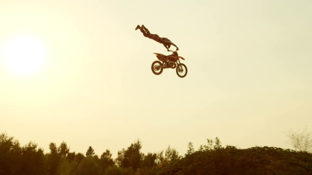 SLOW MOTION: Extreme pro motocross biker jumping over kicker performing a trick at beautiful golden sunset video
