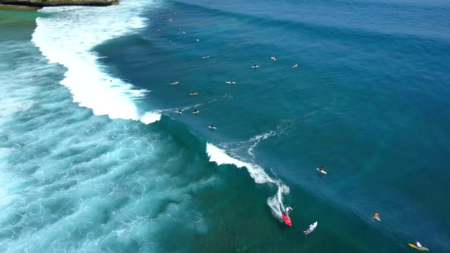 AERIAL: Extreme pro SUP surfer riding big breaking ocean wave in sunny Bali video
