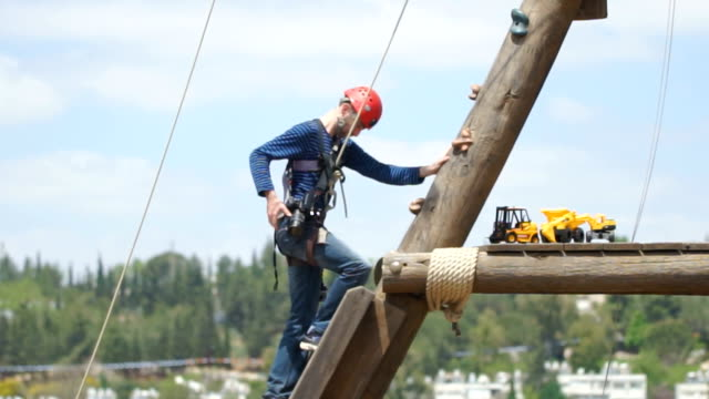 Extreme professional videographer during shooting on climbing tower working under extreme conditions video