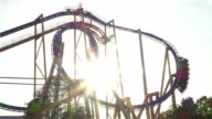 SLOW MOTION: Extreme roller coaster ride at golden sunset video