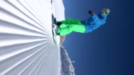 VERTICAL SLOW MOTION: Extreme snowboarder riding on groomed snow in ski resort video