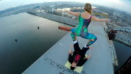 Extreme sport, female balancing on male legs on top of bridge, dangerous hobby video