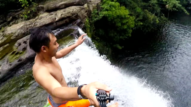 Extremely High POV Cliff Jump into Water above Waterfall Trees and Rocks Below on a Beautiful Sunny Day in Summer in the Forest with a Thumbs Up to Bystanders Extreme Fun Point of View Head Camera video