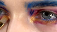 Eye down make-up woman applying eyeshadow, making exotic, two, blue eyebrow, yellow shadow, mascara, finishing touch with special brush, close up, on white, slow motion video