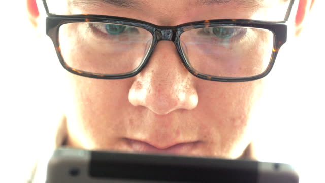 Eyes looking through a pair of glasses at digital tablet video