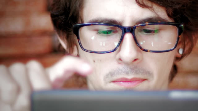 Eyes looking through a pair of glasses at digital tablet video