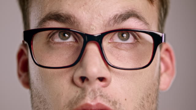 Eyes of a young Caucasian man wearing eyeglasses looking around video