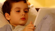 Face of a cute little boy with a tablet PC at home video