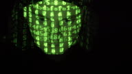 Face of male hacker in hood working on a computer while green code characters reflect on his face in a dark office room. Source code projected over an angry hostile man's face, black background. video