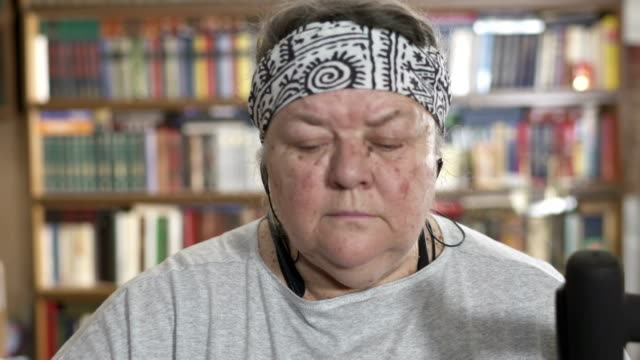Face of obese senior woman exercising on elliptical trainer at home video
