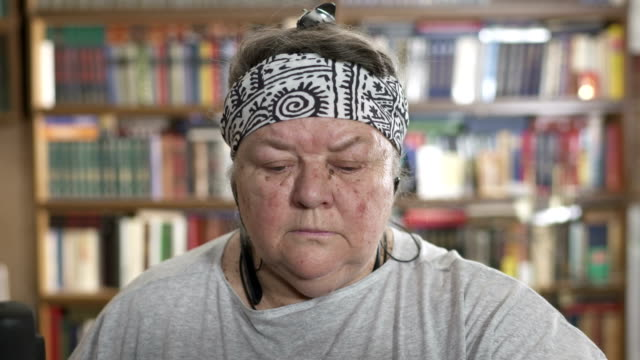 Face of obese senior woman working out on elliptical trainer at home video