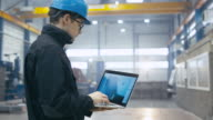Factory worker in a hard hat is using a laptop computer with an engineering software. video
