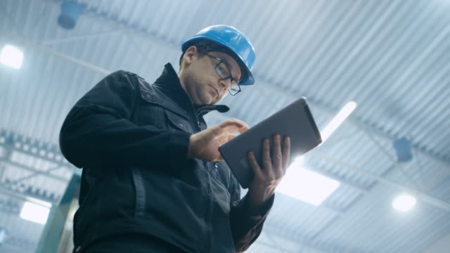 Factory worker in a hard hat is using a tablet computer. video
