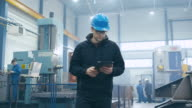 Factory worker in a hard hat is walking and using a tablet computer. video
