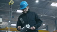 Factory worker is making a quality control of a metal detail with a measuring tool. video