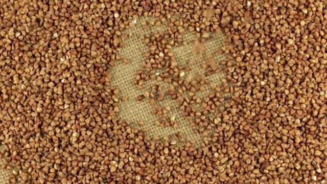 Falling buckwheat grains on the rotating circle of buckwheat lying on sackcloth video