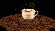 Video of falling coffee beans into mug in real slow motion video