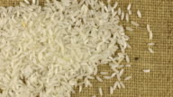Falling grains of rice on a rotating cloth burlap video