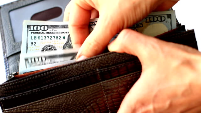 Famale hands counting one hundred dollar bills in wallet video