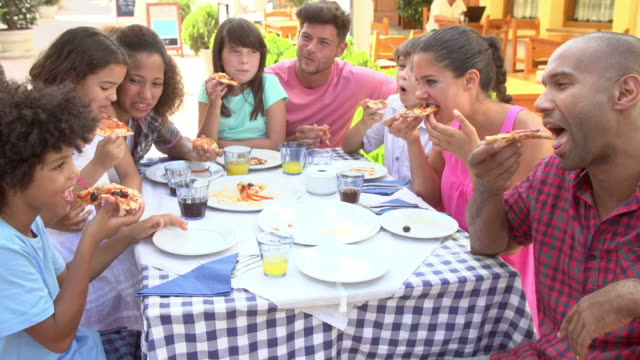 Families Eating Meal At Outdoor Restaurant Together video