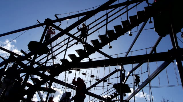Families play on large gorilla climb ropes course silhouette video