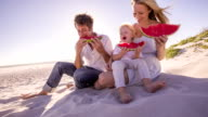 Family at beach eating watermelon video