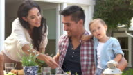 Family At Home Eating Outdoor Meal In Garden video