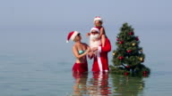Family at tropical beach dancing around the Christmas tree waving their hands video