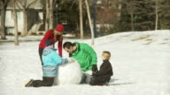 Family buiiding a snowman video