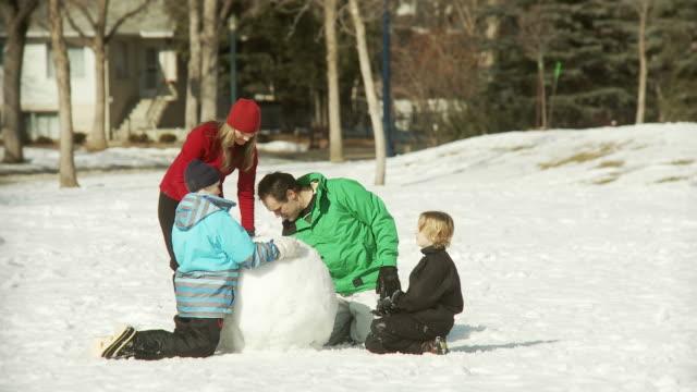 Family buiiding a snowman video