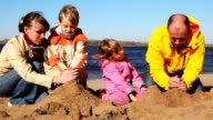 Family build hills of sand together on river beach video