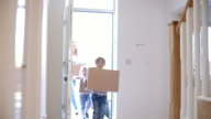 Family Carrying Boxes Into New Home On Moving Day video