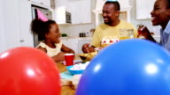 Family celebrating a birthday in kitchen at home video