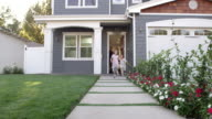 Family Coming Out Of Front Door Of Suburban Home Shot On R3D video