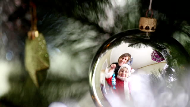 family decorates a Christmas tree video