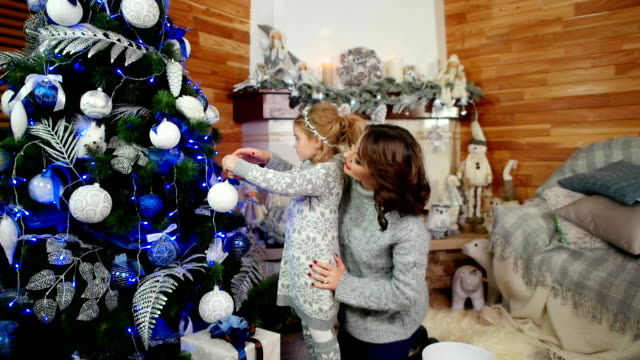 Family decorating a Christmas tree, mother and daughter are preparing for the New Year holiday, happy family at home in the living room in a cozy atmosphere near the fireplace video