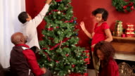 Family decorating Christmas tree together video