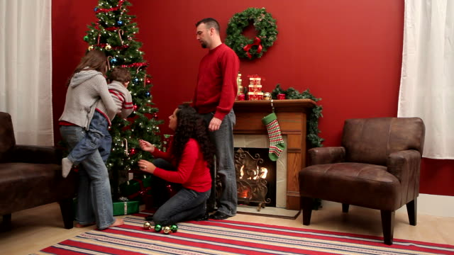 Family decorating Christmas tree video