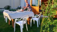 Family dinner on green grass lawn in backyard mother serving table video