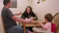 A family eating dinner together at the kitchen table, with a little boy sitting in a high chair booster seat video