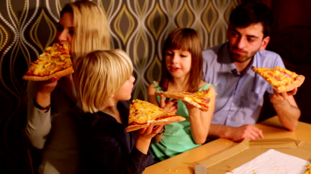 Family eating pizza at home video