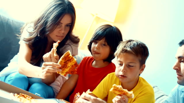 Family eating pizza at home. video