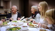 Family enjoying at the dinner table eating and chatting video