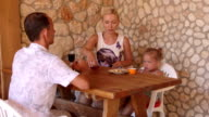 Family enjoying warm days in the outdoor kitchen beside summer house video