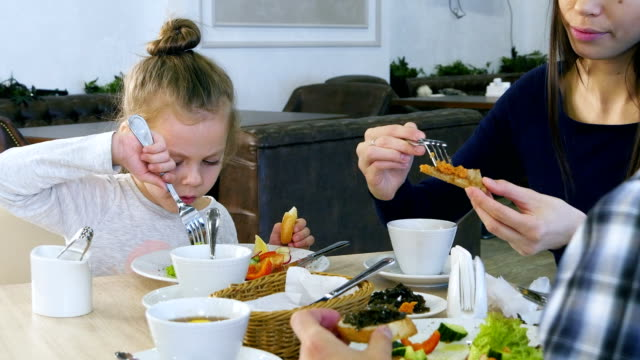 Family have healthy lunch at restaurant. Little daughter eating vegetable salad with white bread video