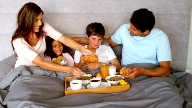 Family having breakfast in bed video