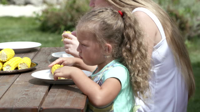 Family having lunch in the garden eating boiled corn on the cob video