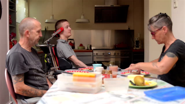 Family having lunch with disabled son video