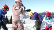 Family Having Snowball Fight On Ski Holiday In Mountains video